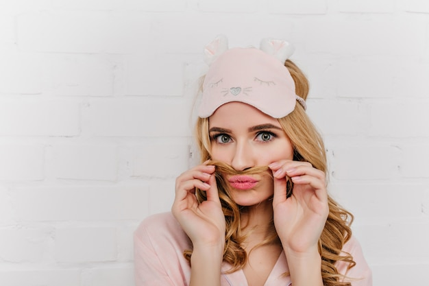 Retrato do close-up de romântica garota pálida na máscara. mulher de cabelos louros positiva usa pijama rosa, posando na parede de luz.