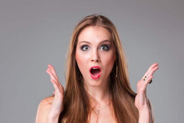 Retrato do close-up de surpresa linda mulher segurando sua cabeça com espanto e boca aberta.