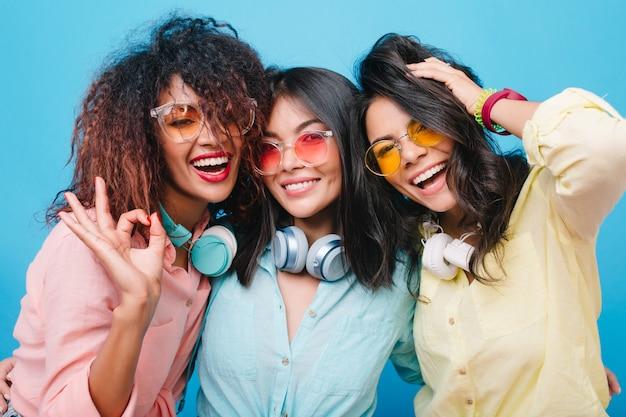 Retrato do close-up de três garotas animadas rindo durante a reunião. foto interna de mulheres bonitas em óculos de sol coloridos, aproveitando o tempo livre juntos.