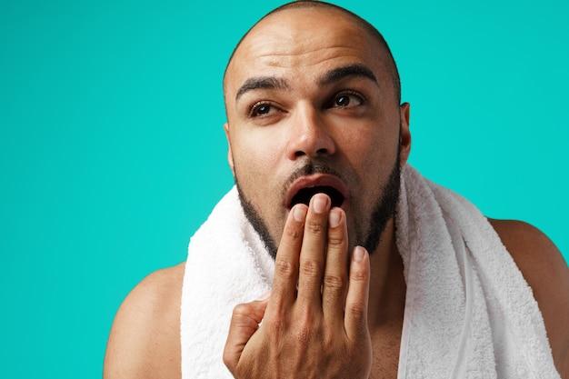 Retrato do close-up de um homem preto com sono com toalha de manhã