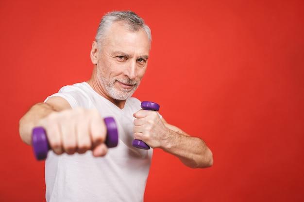 Retrato do close-up de um homem sênior exercitar com halteres contra fundo vermelho