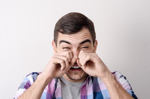Retrato do close-up de um jovem caucasiano, esfrega os olhos com as mãos de lágrimas de riso, tristeza, dor.