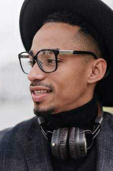 Retrato do close-up de um jovem refinado com pele morena. foto do modelo masculino africano sonhador em óculos e fones de ouvido, refrigeração ao ar livre.