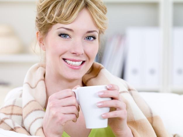 Retrato do close-up de uma bela jovem sorridente e feliz se aquecendo com uma xícara de café quente