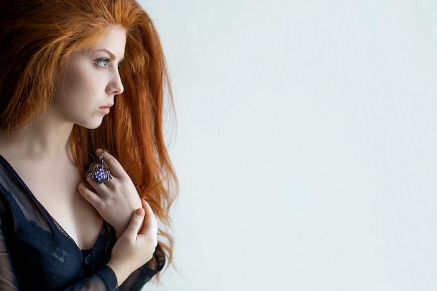 Retrato do close-up de uma bela jovem triste olhando para longe