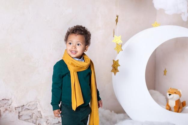 Retrato do close-up de uma cara preta do menino, menino afro-americano. menino preto está sorrindo. bebê fofo, bebê em jogo. sorriso bonito. cabelo encaracolado. mulat. aventuras do pequeno príncipe no mês.
