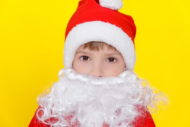 Retrato do close-up de uma criança com uma fantasia de papai noel de ano novo, com uma barba branca artificial.