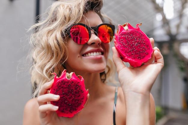 Retrato do close-up de uma deslumbrante menina loira em óculos de sol rosa, posando com frutas exóticas. foto de rir modelo feminino encaracolado com pitaiaiás vermelha.