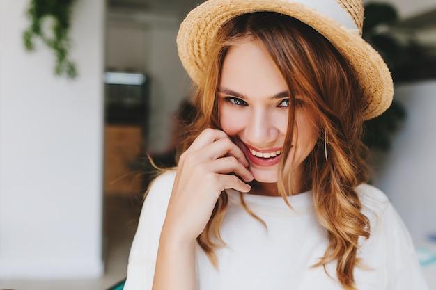 Retrato do close-up de uma garota animada com um penteado elegante sorrindo e tímida tocando o rosto com a mão