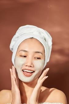 Retrato do close-up de uma garota atraente com uma toalha na cabeça e máscara de argila no rosto isolado sobre fundo laranja.