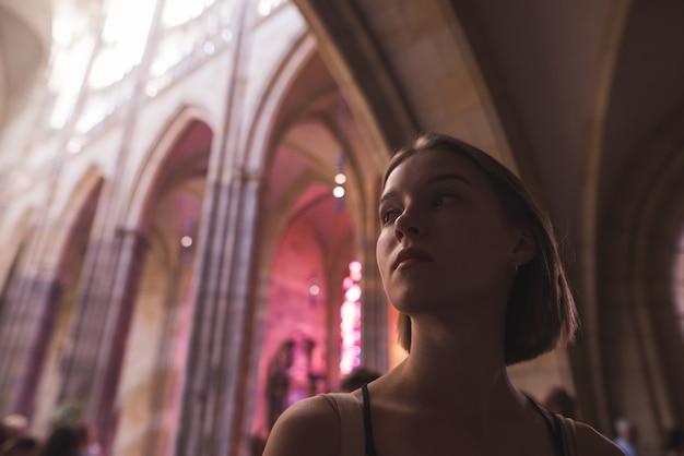 Retrato do close-up de uma garota atraente em pé na antiga igreja histórica