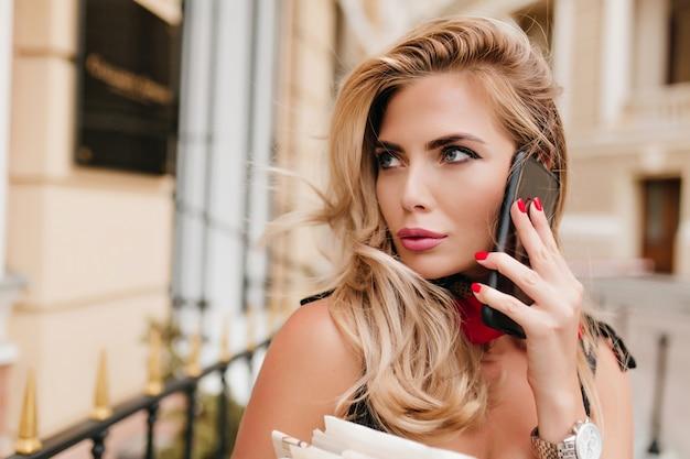 Retrato do close-up de uma garota romântica com lábios rosados falando ao telefone enquanto caminha pela rua
