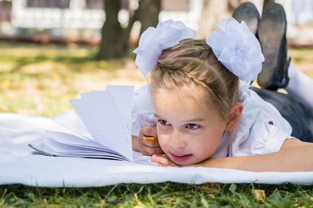 Retrato do close-up de uma garotinha fazendo lição de casa enquanto estava deitado sobre um cobertor em um parque ensolarado de outono. educação ao ar livre para crianças. conceito de volta às aulas
