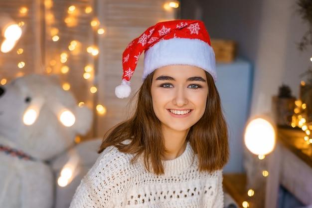 Retrato do close-up de uma jovem bonita rindo com um chapéu de papai noel na cabeça com guirlandas nas mãos dela