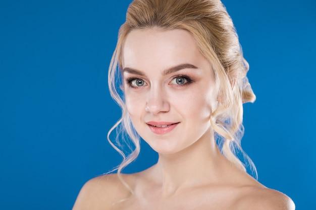 Retrato do close-up de uma jovem garota em um azul