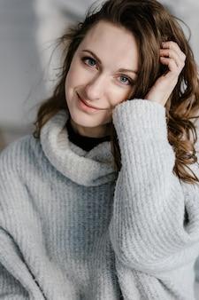 Retrato do close-up de uma jovem muito sorridente numa camisola aconchegante, olhando para a câmera.