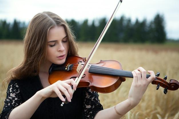 Retrato do close-up de uma jovem mulher com os olhos baixos e tocando violino em um campo de trigo.