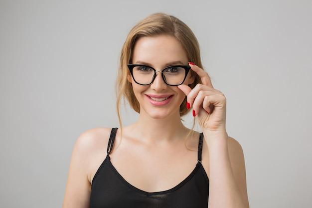 Retrato do close-up de uma jovem mulher sexy atraente em óculos elegantes, inteligente e confiante, estilo elegante, independente, vestido preto, modelo posando em fundo branco do estúdio, isolado
