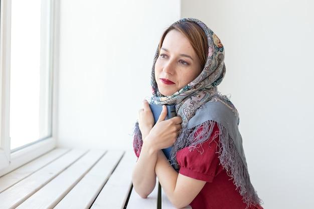 Retrato do close-up de uma jovem sonhadora bonita com um livro na mão, olhando pela janela e pensando em algo. amantes do conceito de clássicos e literatura.