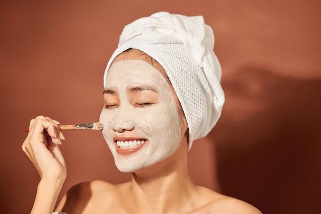 Retrato do close-up de uma linda garota asiática no spa com uma toalha na cabeça, aplicando a máscara de argila facial.