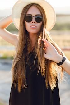 Retrato do close-up de uma linda jovem com longos cabelos escuros usando chapéu de palha, óculos escuros. ela brinca com o cabelo sob os raios quentes do sol poente