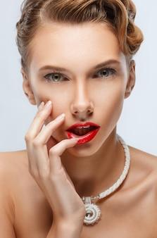 Retrato do close-up de uma linda menina com um colar, uma mão tocou seus lábios