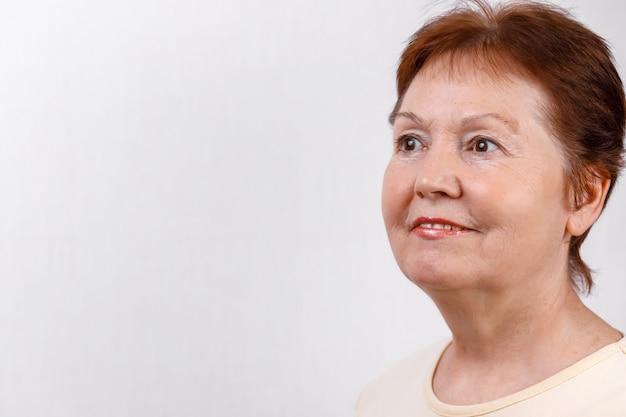 Retrato do close-up de uma linda mulher sênior, olhando para o lado em branco em uma camiseta leve. isolado