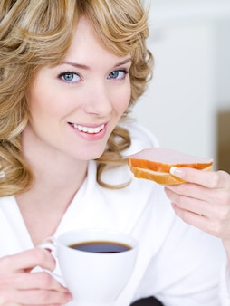 Retrato do close-up de uma linda mulher sorridente e feliz comendo sanduíche e bebendo café
