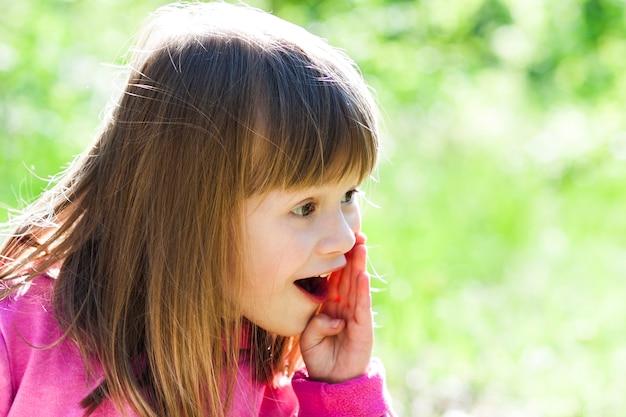 Retrato do close-up de uma menina bonita com expressão do rosto de gritar