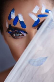 Retrato do close-up de uma menina com maquiagem azul.