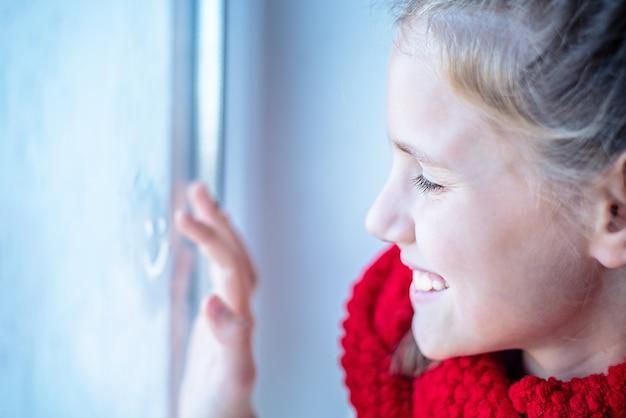 Retrato do close-up de uma menina desenhando um emoji alegre no vidro da janela. imagem de foco seletivo.