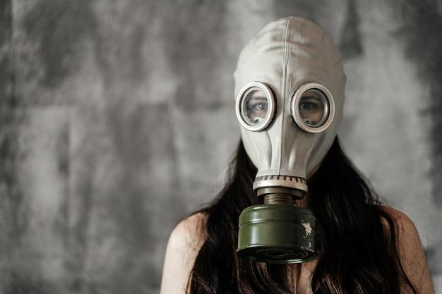 Retrato do close-up de uma menina em uma máscara de gás em um fundo cinza