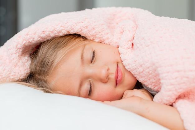 Retrato do close up de uma menina loira deitada e dormindo em uma cama sob um cobertor rosa