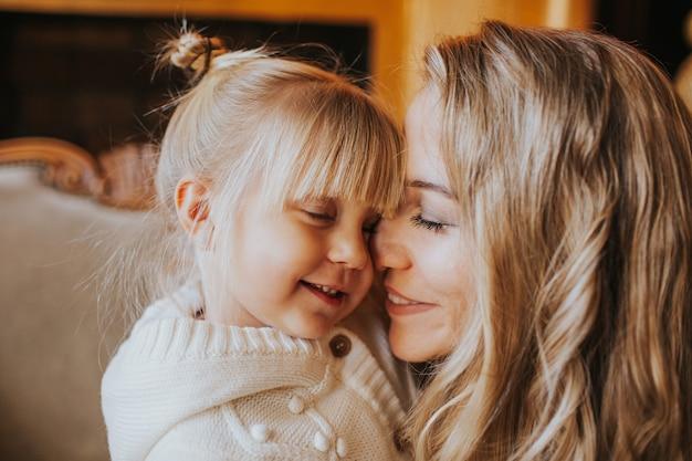 Retrato do close-up de uma menina loira e sua jovem mãe abraçando em casa.