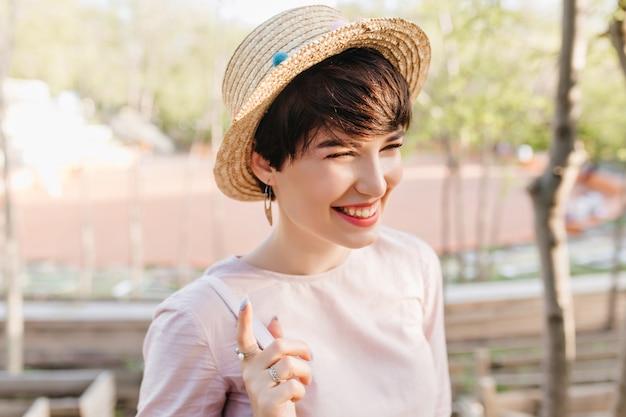 Retrato do close-up de uma menina sorridente, usando um chapéu de palha da moda e anéis, caminhando ao ar livre depois do almoço