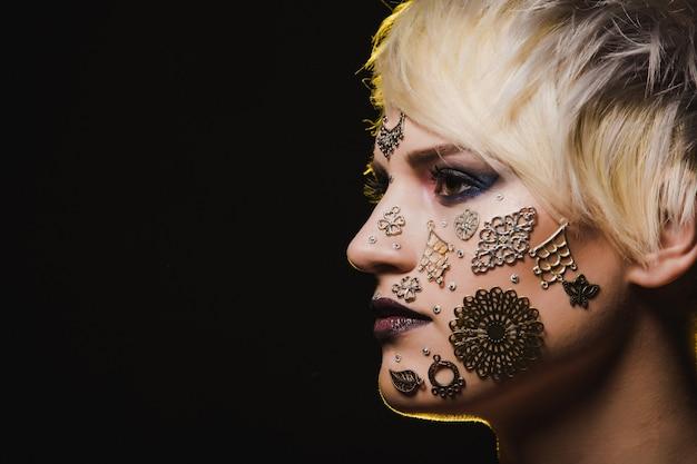 Retrato do close-up de uma mulher bonita com maquiagem abstrata