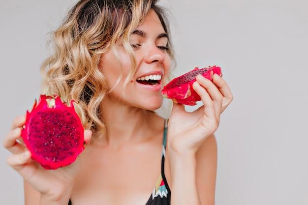 Retrato do close-up de uma mulher bronzeada atraente com penteado curto, comendo fruta do dragão. garota refinada desfrutando de suculenta pitaya vermelha.