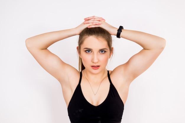 Retrato do close-up de uma mulher da aptidão no branco. braços e ombros fortes de uma garota esportiva