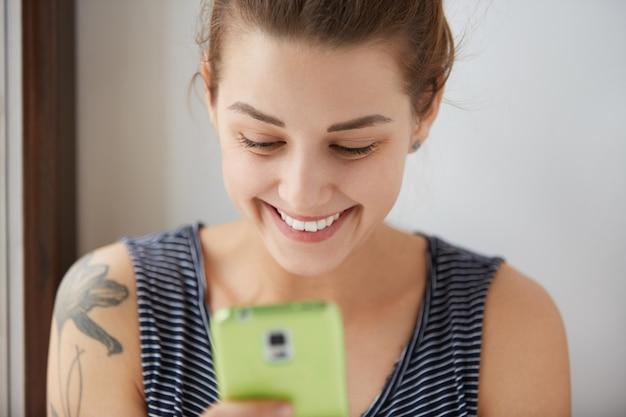 Retrato do close-up de uma mulher de cabelos escuros com pele branca, enviando mensagens para seus amigos na internet. a comunicação social por meio de nossos gadgets pode ser muito divertida e divertida. conceito positivo.