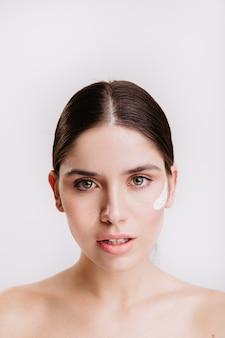 Retrato do close-up de uma mulher de cabelos escuros de olhos verdes, pele saudável e creme no rosto. menina sem maquiagem na parede branca.