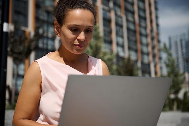 Retrato do close-up de uma mulher hispânica ou afro-americana de meia-idade, mulher de negócios, gerente de escritório, trabalhador, funcionário em trajes casuais, trabalhando no laptop no fundo de edifícios altos