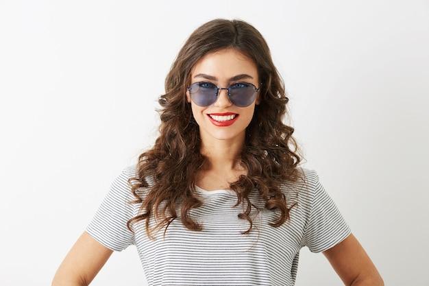 Retrato do close-up de uma mulher jovem e atraente com cabelo encaracolado sorrindo, isolado no fundo branco, usando óculos escuros vestidos com camiseta