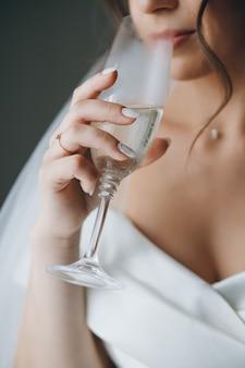 Retrato do close-up de uma mulher linda jovem noiva elegante com uma taça de champanhe, vinho branco, sorrindo e bebendo posando, com um anel no dedo