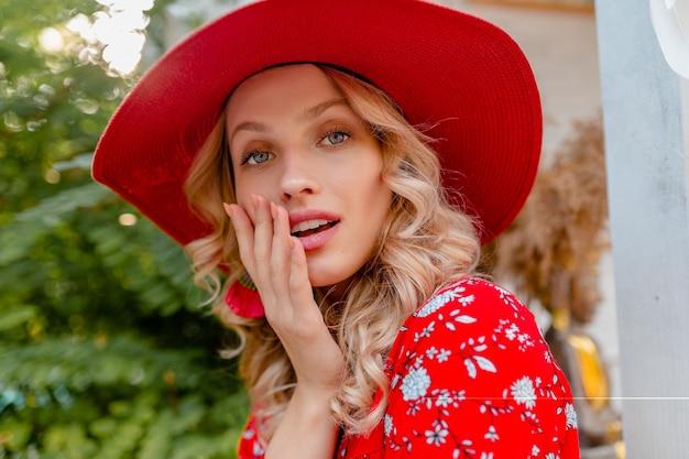 Retrato do close-up de uma mulher loira elegante e atraente sorridente com chapéu vermelho palha e blusa roupa da moda de verão com sorriso sensual
