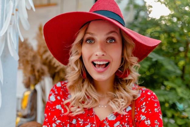 Retrato do close-up de uma mulher loira elegante e atraente sorridente com chapéu vermelho palha e blusa, roupa da moda de verão com sorriso