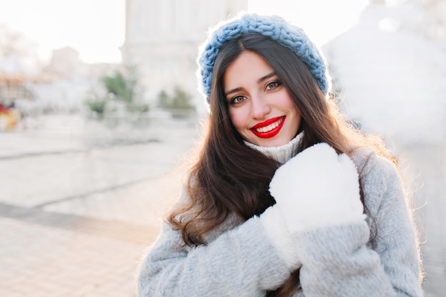 Retrato do close-up de uma mulher morena com lábios vermelhos, sorrindo na cidade de borrão. foto ao ar livre de garota despreocupada com chapéu de malha azul e luvas quentes posando com expressão de rosto surpreso.