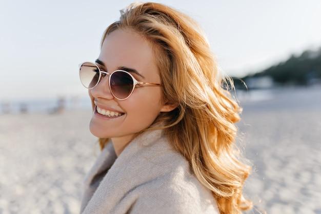 Retrato do close-up de uma mulher positiva com cabelos cacheados ondulados, vestida com um suéter de cashmere bege e óculos escuros na praia.