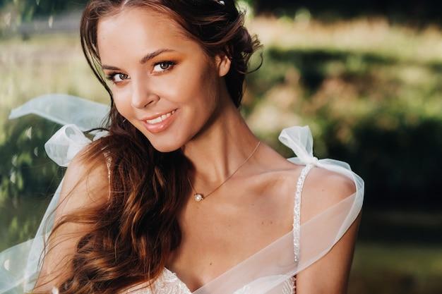 Retrato do close-up de uma noiva elegante em um vestido branco na natureza em um parque natural. modelo em um vestido de noiva e luvas.
