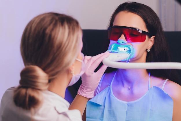 Retrato do close-up de uma paciente do sexo feminino visitando o dentista para clareamento dos dentes na clínica, procedimento de clareamento dos dentes.