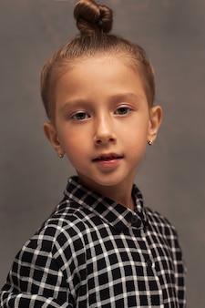 Retrato do close-up de uma pequena menina bonita com cabelo loiro puxado para cima em um coque. a criança brinca e posa. jogos infantis.